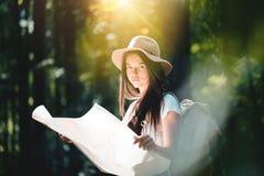 有旅行背包的行家女孩和定位图在看起来定向方式的手上为旅行 免版税图库摄影
