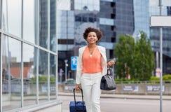 有旅行袋子的愉快的年轻非洲妇女在城市 图库摄影
