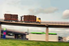 有旅行以在高架桥桥梁的速度的日志的卡车 库存图片