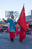 有旗子的亚裔中国妇女在115th每年金黄龙 库存图片