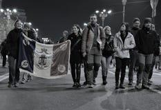 有旗子的人在从布加勒斯特的街道上