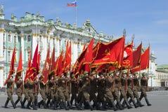有旗子的战士在宫殿正方形 游行排练以纪念胜利天在圣彼德堡 免版税库存照片