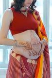 有无刺指甲花纹身花刺的孕妇腹部 免版税库存照片