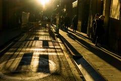 有无法认出的人的街道有大反差和黑暗的背景 免版税库存照片