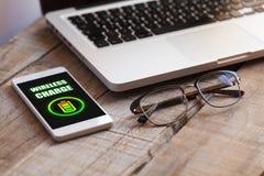 有无线充电的手机在一个木工作场所 免版税库存图片
