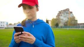 有无线耳机和智能手机的妇女选择音乐并且通过体育场跑在日落 慢的行动 股票视频