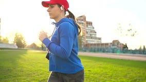 有无线耳机和智能手机的妇女选择音乐并且通过体育场跑在日落 慢的行动 股票录像