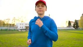 有无线耳机的妇女通过体育场跑在日落 慢的行动 影视素材