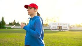 有无线耳机的妇女通过体育场跑在日落 慢的行动 股票录像