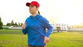 有无线耳机的妇女通过体育场跑在日落 股票视频
