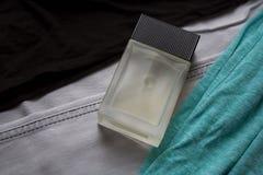 有无袖衫和牛仔裤的玻璃香水瓶 库存照片