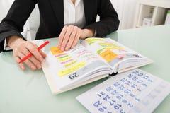 有日历文字日程表的女实业家在日志 免版税图库摄影