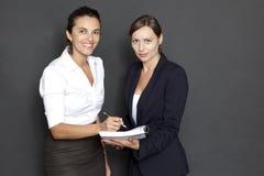 有日常文书工作的二名女实业家 免版税库存照片
