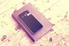 有日志和叶子的空白的手机屏幕在木桌上 免版税库存图片