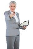 有日志的女实业家把她的手指指向的照相机 免版税库存图片