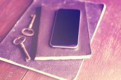 有日志的空白的智能手机和在木地板上的老牌钥匙 库存照片