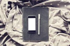 有日志的空白的智能手机在围巾的屏幕和笔 库存图片