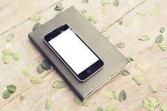 有日志的空白的智能手机屏幕在与叶子的木桌上, 免版税库存照片