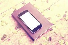 有日志的空白的白色屏幕智能手机在与le的木桌上 库存照片