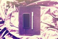 有日志的空白的黑手机在围巾的屏幕和笔有d的 图库摄影