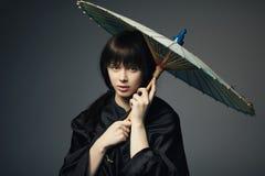 有日本伞的美丽的女孩 库存照片