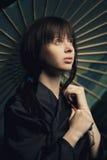 有日本伞的美丽的女孩 库存图片