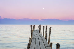 有日落天空的木小船船坞在背景在湖Atitlan,危地马拉 库存照片