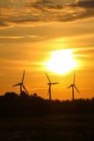 有日落日出的三台风车 库存图片