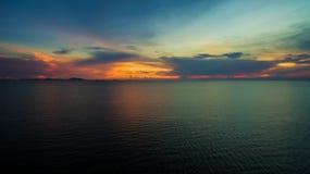 有日落暮色天空的美妙的黑暗的银色海在晚上时间 免版税图库摄影