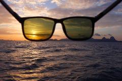 有日落的太阳镜在海 免版税库存图片