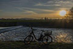 有日落的黑电自行车在Malse河的测流堰附近 库存图片