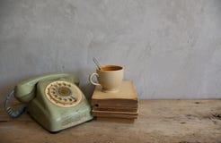 有旧书和电话的一个杯子在木头 库存照片