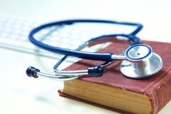有旧书和膝上型计算机的医疗听诊器在桌上 免版税库存图片