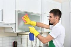 有旧布的男性管理员清洁厨房家具 图库摄影
