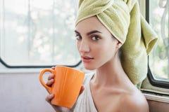有早晨杯子的美丽的少妇热的饮料 免版税库存照片