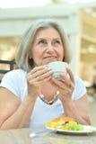 有早餐和咖啡的老妇人 免版税库存照片