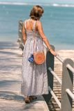 有时兴的时髦的外面藤条袋子橙色颜色和丝绸围巾的妇女 巴厘岛,印度尼西亚热带海岛  免版税库存图片