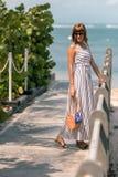 有时兴的时髦的外面藤条袋子橙色颜色和丝绸围巾的妇女 巴厘岛,印度尼西亚热带海岛  免版税库存照片