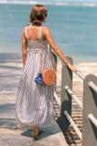 有时兴的时髦的外面藤条袋子橙色颜色和丝绸围巾的妇女 巴厘岛,印度尼西亚热带海岛  库存图片