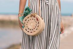 有时兴的时髦的外面藤条袋子裸体颜色和丝绸围巾的妇女 巴厘岛,印度尼西亚热带海岛  藤条 免版税库存照片