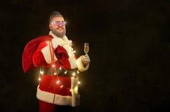 有时兴的理发的圣诞老人与一杯香槟 免版税库存照片