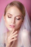 有时尚婚礼发型的美丽的新娘-在桃红色背景 年轻华美的新娘特写镜头画象  婚姻 演播室sho 免版税图库摄影
