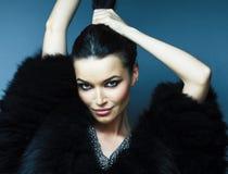 有时尚构成摆在的年轻俏丽的深色的女孩典雅在有首饰的毛皮大衣在蓝色背景,生活方式 库存照片
