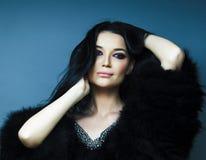 有时尚构成摆在的年轻俏丽的深色的女孩典雅在有首饰的毛皮大衣在蓝色背景,生活方式 免版税库存图片