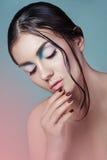 有时尚湿发型和美好的构成的深色的女孩在蓝色有桃红色作用背景 免版税库存照片
