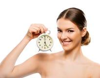有时钟关闭的美丽的妇女,微笑 免版税库存照片