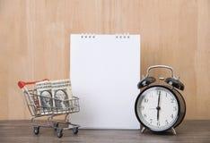 有时钟和推车购物的空白的日历计划者在木书桌上 免版税库存图片