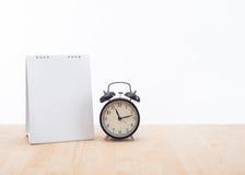 有时钟和木头书桌办公室的空白的日历计划者 免版税图库摄影
