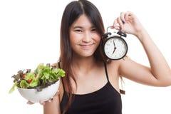 有时钟和沙拉的年轻亚裔妇女 库存图片