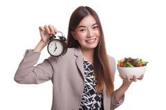 有时钟和沙拉的年轻亚裔妇女 免版税库存照片